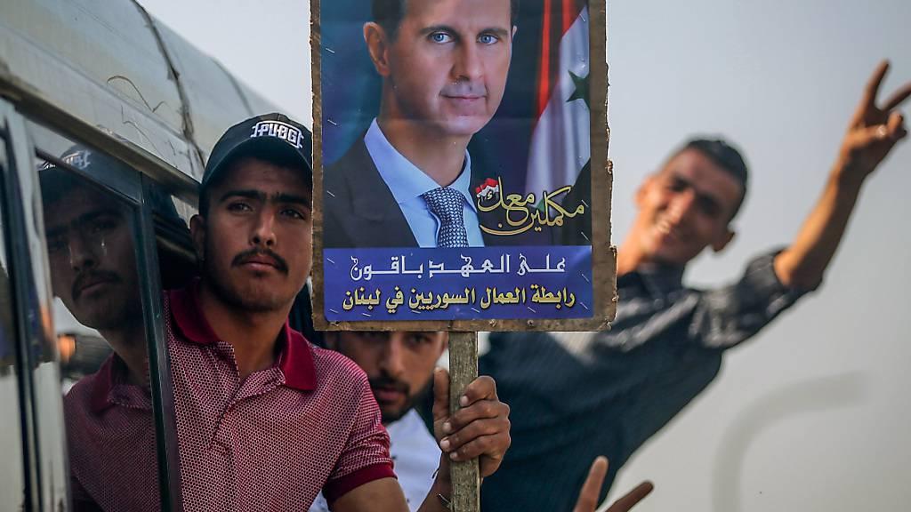 Ein Syrer hält ein Bild des syrischen Präsidenten al-Assad. Er und weitere Wähler machen sich auf den Weg, um ihre Stimmen abzugeben. Vor der syrischen Präsidentschaftswahl am 26. Mai hat in den Botschaften im Ausland die Stimmabgabe begonnen. Foto: Marwan Naamani/dpa Foto: Marwan Naamani/dpa
