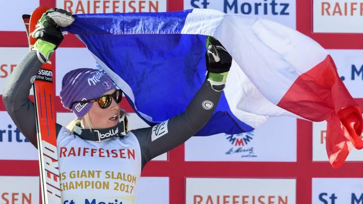 Die Weltmeisterin hält stolz ihre Landesflagge hoch.