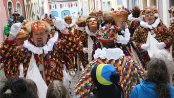 Die Narro-Altfischerzunft 1386 Laufenburg verteilt in ihren Blätzli-Kleidern beim Narrenlaufen Weggen und Orangen.