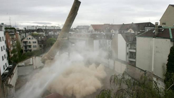 Die Schweizer Industrie steht im Kampf gegen zahlreiche Hindernisse: Sprengung eines Hochkamins in Basel. Foto: Keystone