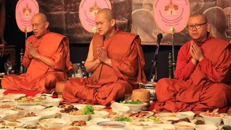 Die Besucher der Zeremonie haben ihr mitgebrachtes Essen in Dutzenden Schalen vor die Mönche gelegt.