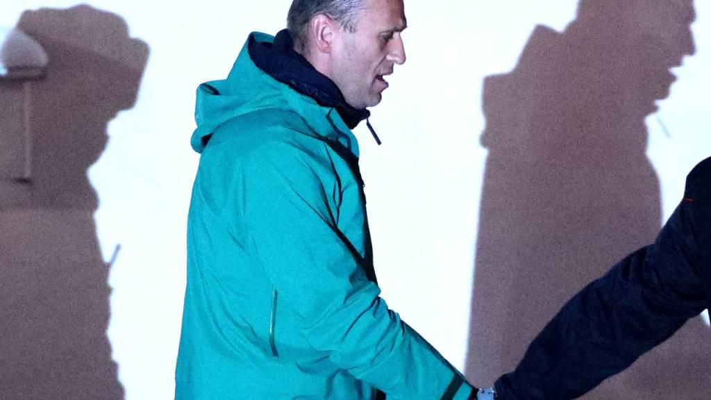 Alexej Nawalny, Oppositionspolitiker und Kremlkritiker, wird von einem Polizeibeamten vor der 2. Abteilung der Direktion des russischen Innenministeriums von Chimki eskortiert. Foto: Sergei Bobylev/TASS/dpa