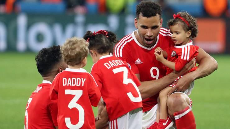 Hal Robson-Kanu mit seiner Tochter auf dem Arm und im Gespräch mit den Kindern seines Teamkollegen Neil Taylor.