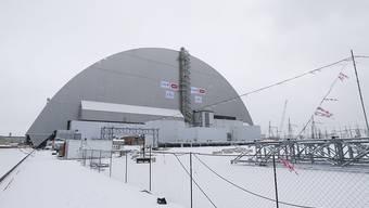 Die neue Schutzhülle um die Atomruine in Tschernobyl steht. Sie wurde mit einem Hydrauliksystem auf Spezialschienen über den havarierten Reaktor geschoben.