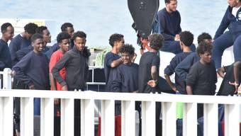 Flüchtlinge warten in Italien auf den Landgang. Es kamen 2018 bisher deutlich weniger von ihnen über das Mittelmeer als in den Vorjahren. (Archiv)