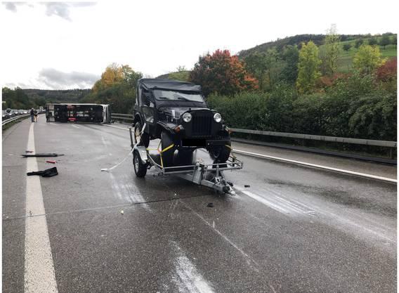 Das gekippte Wohnmobil und der von ihm getrennte Anhänger samt aufgeladenem Jeep nach dem Unfall.