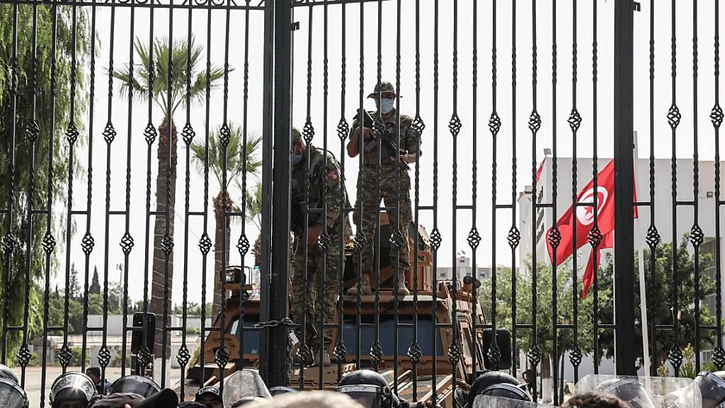 Soldaten der tunesischen Armee bewachen den Eingang des Parlamentsgebäudes während einer Demonstration einen Tag nachdem der tunesische Präsident Saied den Premierminister Hichem Mechichi abgesetzt hat. Die Arbeit des Parlaments ist zunächst für 30 Tage eingefroren. Foto: Khaled Nasraoui/dpa