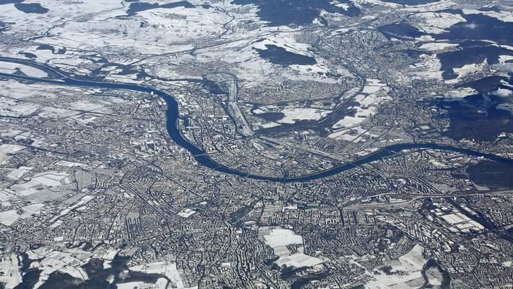 Luftaufnahme der winterlichen Stadt Basel: Aus der Luft ist schön sichtbar, wie weit die Stadt nach Deutschland und Frankreich gewachsen ist.
