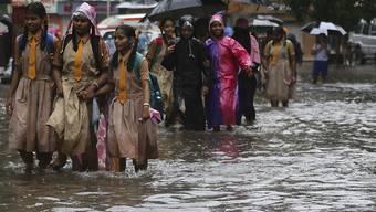 Schulkinder waten in der Millionenstadt Mumbai durch eine vom Monsunregen überschwemmte Strasse.