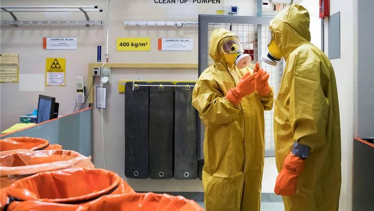 Gelbe Schutzanzüge und Luftfiltermasken: Mitarbeitende des Kernkraftwerks Mühleberg bringen den Reaktor ein letztes Mal auf Hochtouren.
