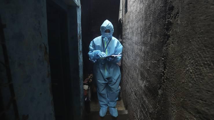 Ein Mitarbeiter des Gesundheitswesens geht in einem Slum, um bei den Bewohnern einen Corona-Test durchzuführen. Foto: Rafiq Maqbool/AP/dpa