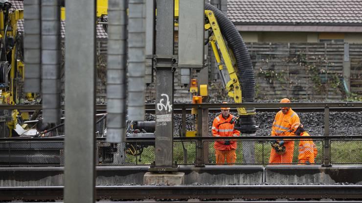 Mitarbeiter der SBB saugen mit einem Sauglastwagen auf einem Bahnflachwagen den kontaminierten Schotter und das gebundene Öl ab.
