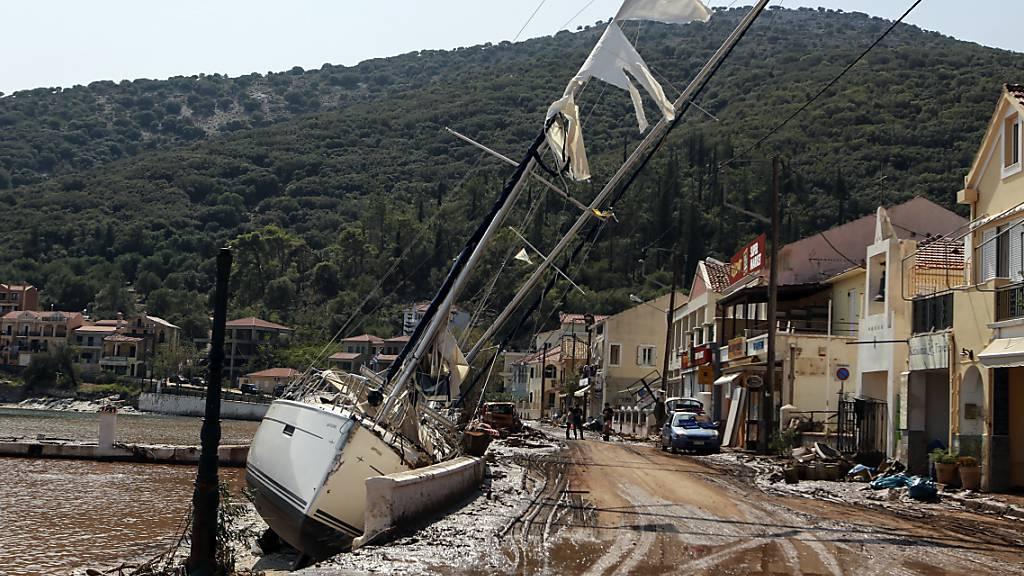 Eine Segelyacht liegt nach einem Sturm neben einer Straße an Land. Der Wirbelsturm «Ianos» und ein weiteres Sturmtief über der Nordägäis haben in weiten Teilen Griechenlands schwere Schäden verursacht. Foto: Nikiforos Stamenis/AP/dpa