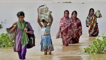 Bewohnerinnen des Burdwan-Distrikts im indischen Westbengalen retten ihren Besitz vor den Fluten, die der Monsun mit sich brachte.