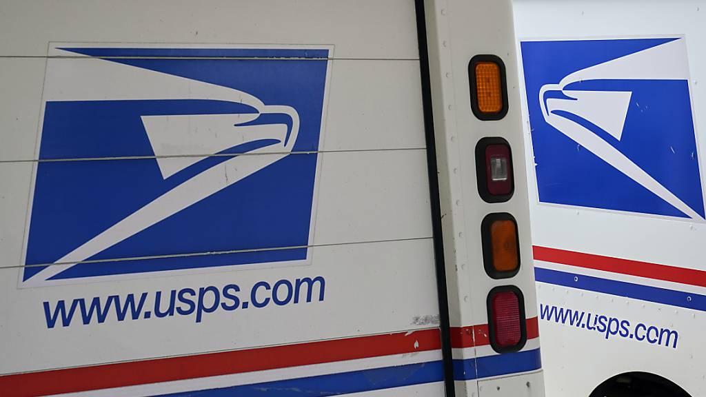 Postzustellfahrzeuge sind vor einem Postamt geparkt. Foto: Nati Harnik/AP/dpa