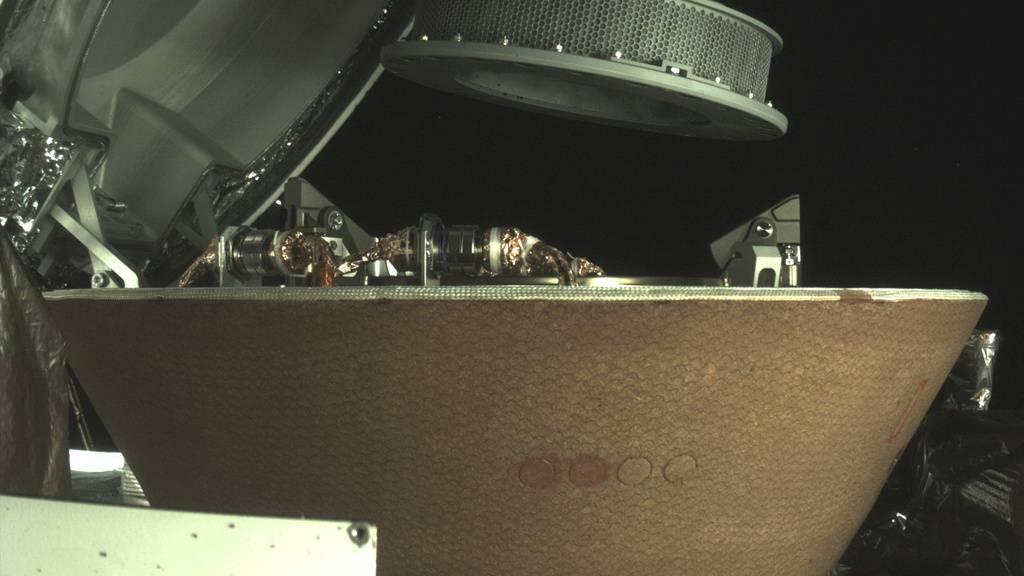 Der Sammelbehälter (rund, gelocht) schwebt über der Probenkapsel in der Raumsonde Osiris-Rex. Nachdem der Behälter wegen undichtem Deckel Teile des eingesammelten Staubs verloren hat, wurde der Rest jetzt erfolgreich gesichert. (Bild Nasa)