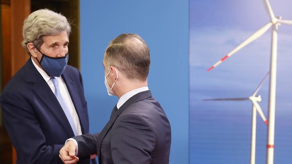 Der deutsche Außenminister Heiko Maas (SPD, r) begrüßt in Berlin den Sondergesandten des US-Präsidenten für das Klima, John Kerry (l). Foto: Odd Andersen/AFP Pool/dpa
