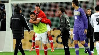 Orham Ademi schleppt Torschütze Josip Drmic nach dem 1:1 im Hinspiel gegen Deutschland vom Feld.