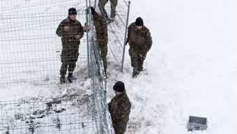 Offener Diskussionsgeist in Hochsicherheitsatmosphäre: Schweizer Soldaten montieren im Vorfeld des WEF Gitterzäune.KEY