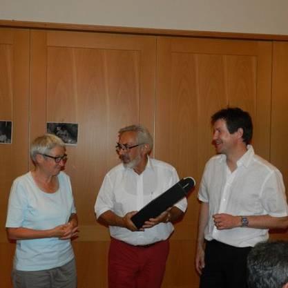 Der Referent und die Mitorganisatorin werden von Ueli Jehle mit einem Präsent geehrt.