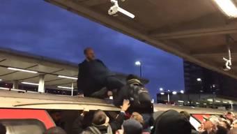 Hier wird einer der Klimaaktivisten von einem Pendler vom U-Bahndach gezogen