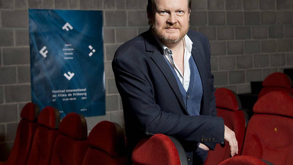 Thierry Jobin, der Direktor des Internationalen Filmfestivals Freiburg FIFF vor dem Plakat der 31. Ausgabe, die am 31. März eröffnet wird.