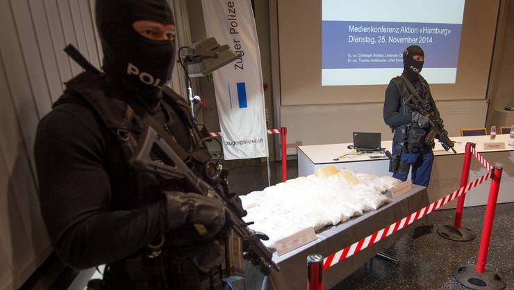 Zwei Polizeibeamte beschützen während der Medienkonferenz der Zuger Polizei die beschlagnahmten 55 Kilogramm Heroin.