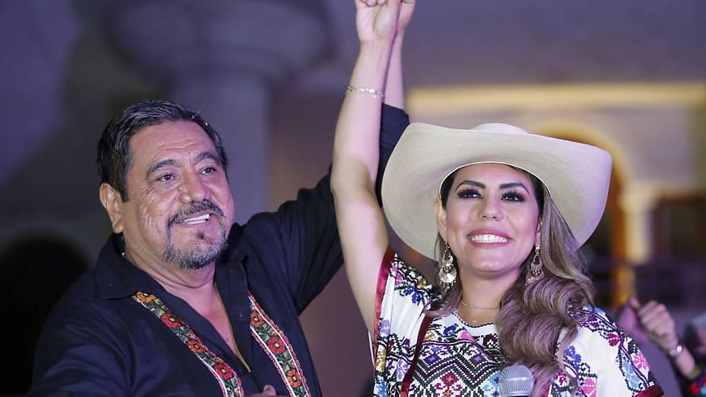 Evelyn Salgado, die für die regierende Morena-Partei als Gouverneurin des Bundesstaates Guerrero kandidiert, und ihr Vater Felix Salgado begrüßen Anhänger während einer Kundgebung zur Feier ihrer Wahl auf dem Zocalo-Platz. Salgado kandidiert anstelle ihres Vaters, Felix Salgado Macedonio, nachdem das Wahlgericht die Streichung seines Namens von den Stimmzetteln angeordnet hatte, weil er gegen die Vorschriften für Wahlkampfausgaben verstoßen hatte. Foto: Fernando Llano/AP/dpa