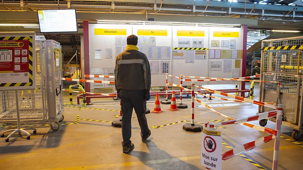 Die Corona-Krise wirkt sich auf den Gewinn der Post aus. Im Bild ein Mann im Paketzentrum Daillens im Kanton Waadt. (Archivbild)