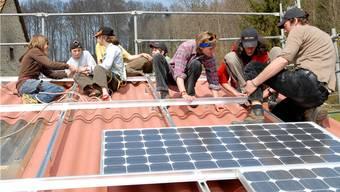 Jugendliche montieren zusammen mit Nationalrätin Maya Graf Solarpanels.