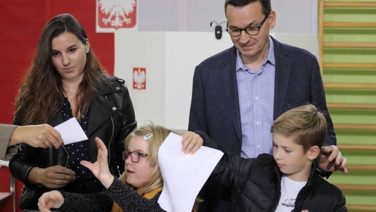 Polens Ministerpräsident Mateusz Morawiecki mit Familie am Sonntag bei der Stimmabgabe - die Regierungspartei Recht und Gerechtigkeit (PiS) von Morawiecki errang bei der Parlamentswahl ersten Prognosen zufolge einen klaren Sieg.