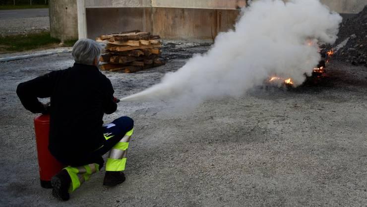 Mit einem Feuerlöscher wird ein Feuer aus nötiger Distanz  gelöscht.