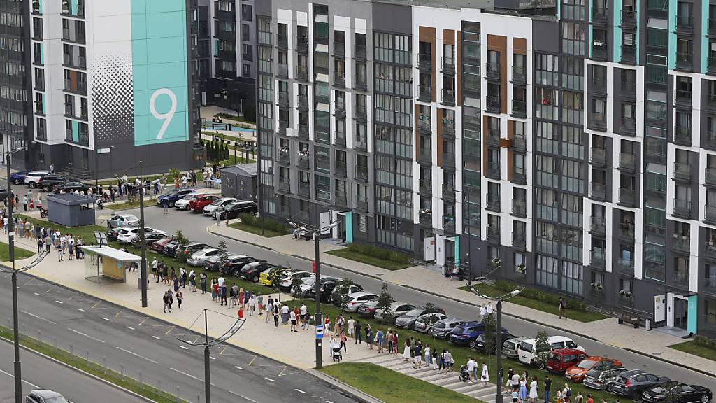 Menschen stehen auf einem Gehweg an einem Wahllokal in Minsk Schlange. Foto: Sergei Grits/AP/dpa
