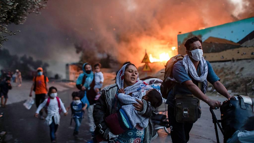 ARCHIV - Migranten fliehen vor einem erneuten Feuers mit ihren Habseligkeiten aus dem Flüchtlingslager Moria. Foto: Petros Giannakouris/AP/dpa