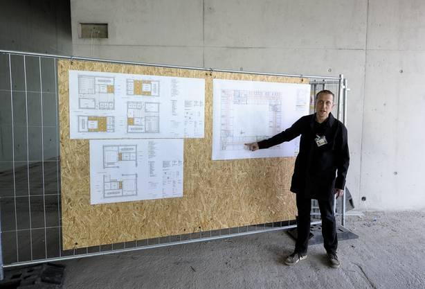 Projektleiter Jörg Kreienbühl erklärt den Aufbau des Gebäudes anhand der Pläne.