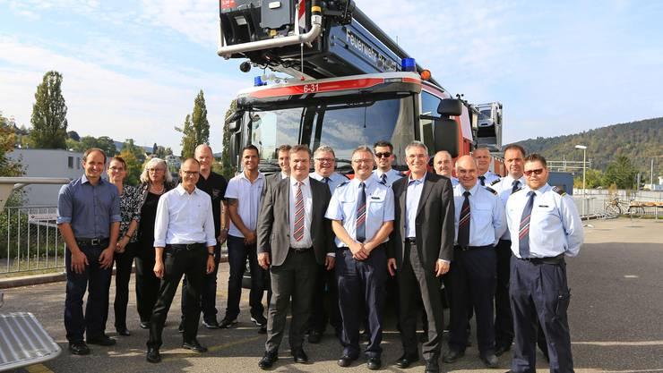 Gebäudeversicherungsdirektor Sven Cattelan (im Anzug, links) und Feuerwehrinspektor Werner Stampfli (rechts daneben) freuen sich zusammen mit dem Beschaffunsgteam und den Feuerwehrkommandanten über die jüngsten beiden der rund 80 kantonalen Einsatzfahrzeuge.
