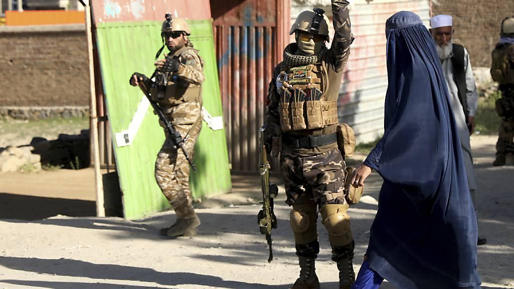 Sicherheitskräfte arbeiten am Anschlagsort nördlich der Hauptstadt Kabul im Distrikt Schakar Dara. Bei dem Anschlag sind mindestens zwölf Menschen getötet worden. Foto: Rahmat Gul/AP/dpa