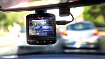 Eine sogenannte Dashcam, befestigt an der Windschutzscheibe, filmt den Strassenverkehr aus einem Auto.
