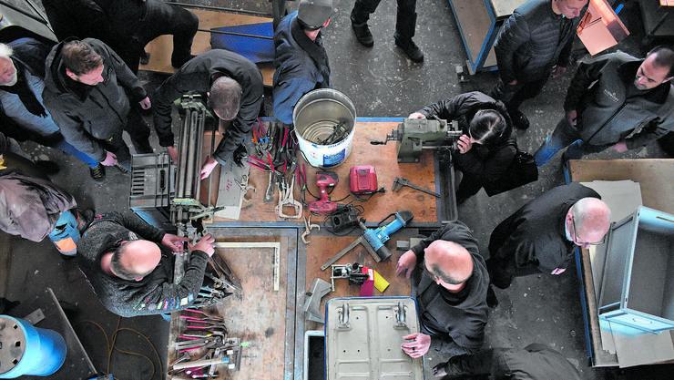 Zangen, Schraubenschlüssel und Maschinen werden von den Käufern eingepackt und abmontiert.