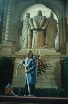 1980: Eine Frau staubsaugt den Teppich vor dem Ehrenmal der «Drei Eidgenossen» in der Eingangshalle des Bundeshauses.