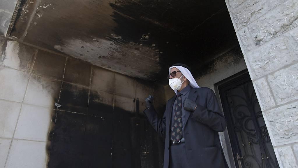 Ein Palästinenser mit Mundschutz inspiziert die verbrannten Mauern der Moschee. Foto: Nasser Nasser/AP/dpa