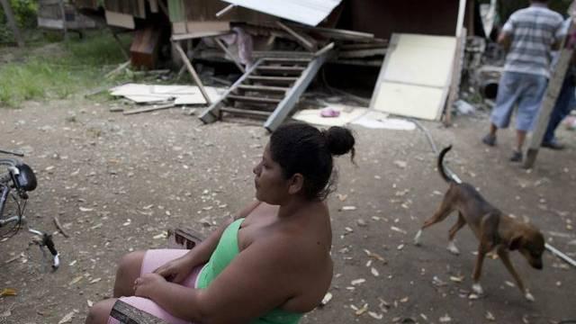 Frau sitzt neben ihrem zerstörten Haus (Archivbild)