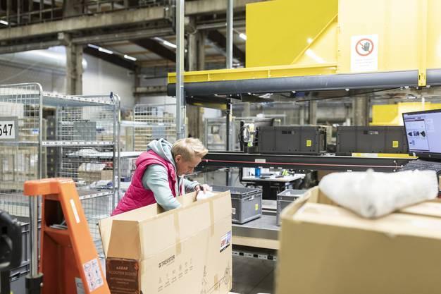 Die Schachteln werden ausgepackt und Produkte sortiert.