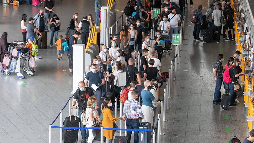 Passagiere warten auf dem Flughafen. Ab dem 1. August müssen auch Passagiere, die nach Deutschland zurückkehren, einen negativen Corona-Test vorlegen. Foto: Boris Roessler/dpa