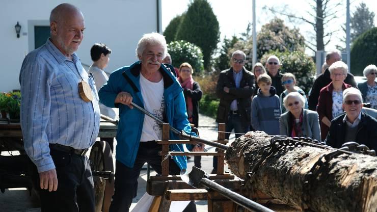 Obmann Oscar Bamert und Thomas Kasapidis vom Ortsmuseum zeigen anlässlich der Vernissage zur Trinkwasserausstellung, wie früher sogenannte Teuchel, hölzerne Wasserleitungsrohre, von Hand mit dem Teuchelbohrer gefertigt wurden.