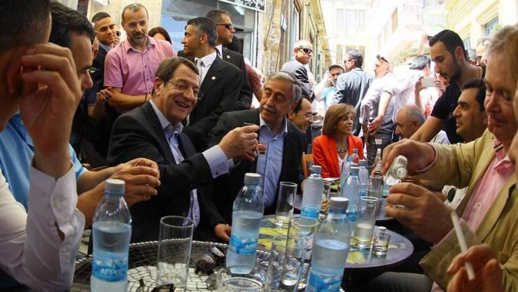 Zypern erhält Rettungsgeld vom IWF: Volksgruppenführer der türkischen und griechischen Zyprer, Mustafa Akinci (Mitte) und Nikos Anastasiades stossen an (Symbolbild)