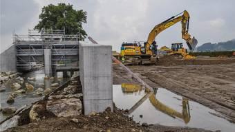 Das Durchlassbauwerk (links) ist bereits fertig betoniert, zurzeit sind die Arbeiten für die Aufschüttung des Querdamms im Gang.