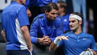 Rafael Nadal und Roger Federer beraten sich während eines Spiels im Laver Cup. Aber wohl kaum über ihren Rücktritt, wie John McEnroe scherzt (Bild: Keystone).