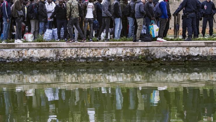 Flüchtlinge stehen Schlange, um in Unterkünfte in Paris oder der Umgebung gebracht zu werden. Seit Monaten hatten sich immer mehr Migranten an den Ufern zweier Kanäle im Nordosten der französischen Hauptstadt angesiedelt.