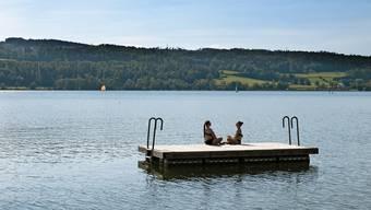 Zwei junge Frauen geniessen das schöne Spätsommerwetter auf einem Floss auf dem Greifensee.